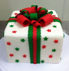 Gift themed Christmas cake. The cake is decorated to look like a Christmas gift complete with stars as the wrapper decoration and a red and green Christmas bow.