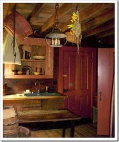 FARMHOUSE – INTERIOR – vintage early american farmhouse showcases raised panel walls, barn wood floor, exposed beamed ceiling, and a simple style for moulding and trim, like in this farmhouse.