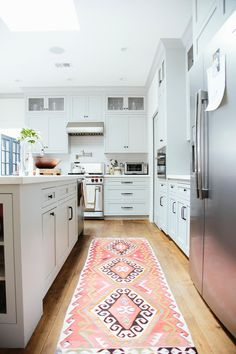 Love this all-white kitchen with silver appliances, dark bronze hardware, light hardwood floors and a pop of color from the vintage pink and orange kilim runner rug down the center. From the Simone LeBlanc Home Tour shot by Paige Jones.