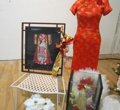 Gifts with Asian theme Christmas tree.  Red dress, framed picture, doll and feather wreath.