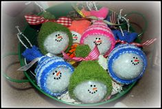 I used clear glass ornaments.  Most of them I filled with fake snow, but I also did a few adding white paint inside the ornament.  You can see the difference in the top picture.  I stamped on a snowman face with StazOn, but then also went over it with a black sharpie paint pen.  I also painted on the nose with an orange paint pen.  The hats were made using a baby sock.  I cut a hole in the sock so you can attach string/ribbon to hang your ornament.  Then closed off the top with some ribbon