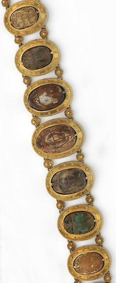 An antique faience and fourteen karat gold scarab bracelet  designed with links of graduating oval-shaped carved scarabs, set within a frame of beaded gold, each separated by round gold links; accompanied by original fitted box; length: 7 3/8in.