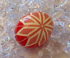 This beautiful traditional Pysanky egg is finished in red and white. The egg has been dyed using the the traditional Ukrainian batik method. Designs are created by applying dyes in layers using melted beeswax. Upon completion, the egg is covered with a thin layer of clear gloss urethane,