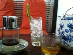 coffee with milk (brown coffee), a cup of ice with water morning glory straw at Cuc Gach cafe