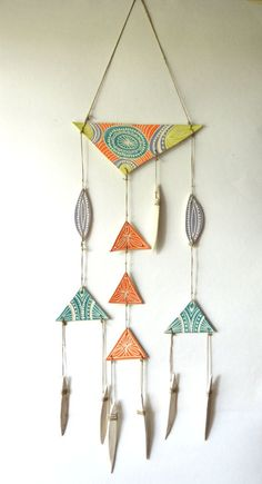 Hand carved ceramic wall hanging in bright fun summer colors. Pieces are all hand tied using natural hemp cords. Can be hung indoors or out doors. Can
