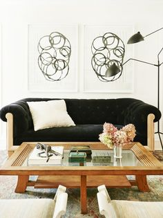 Tufted black and wood sofa, abstract wall art, and wooden and glass coffee table with antique decor. Home Living Room, Living Room Designs, Living Spaces, Beverly Hills Houses, Design Salon, Wood Sofa, White Walls, Interior Inspiration, The Help