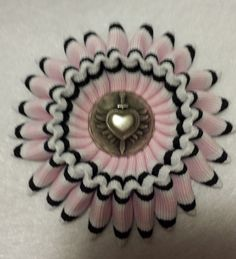 Pink, black, and white cocarde with a pewter button center. A break from my more military looking ribbons.