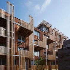 Vertical timber slats provide shade and privacy for staggered balconies arranged across the facade of this east London housing by Brady Mallalieu Architects