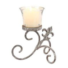 """2 votive candleholders with scrolling bases with fleur-de-lis accents.  Product: Set of 2 candleholdersConstruction Material: Glass and ironColor: AmberAccommodates: (1) Candle each - not includedDimensions: 5.75"""" H x 4.75"""" W x 4.75"""" D each"""