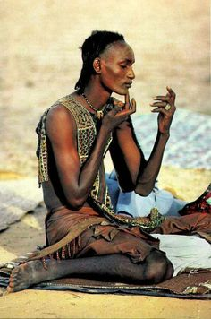 Niger, Africa  'Absorbed in preening', a young man with his hairline shaved to dramatize his forehead applies power to lighten his skin for the Yaake dance, when the women judge men on charm and beauty by Carol Beckwith #SkinLighteningMen