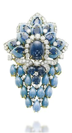 A TURQUOISE, SAPPHIRE AND DIAMOND BROOCH, BY CUSI  Centering upon a cabochon sapphire, in a brilliant-cut diamond surround, extending carved turquoise and pear-shaped sapphires trimmed with brilliant-cut diamonds, and suspending drop-shaped turquoises, cabochon sapphires and diamond-set scrolling details, mounted in gold, 7.3 cm Signed Cusi
