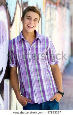 Young guy leaning on graffiti wall