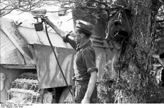A German soldier spray painting a Jagdpanther tank destroyer for camouflage, France, June 1944