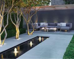 Fint med: fontänen, plattorna, träden som växer i fyrkanter med vit sten i, belysningen underifrån på träden, kantiga buskar