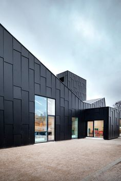 A sawtooth roof with integrated skylights and solar panels gives this library and cultural centre in Denmark an industrial aesthetic that references its location at an old furniture factory Black Architecture, Factory Architecture, Contemporary Architecture, Architecture Details, Minimalist Architecture, Cladding Design, Exterior Cladding, Building Facade, Building Design