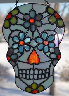 Beautiful stained glass Day of the Dead sugar skull or calavera. These decorative skulls are traditionally made from sugar or clay and are used in the Mexican celebration of Dia de los Muertos and All Souls Day. This stained glass sugar skull is made from 80+ pieces of high quality glass using the copper foil method. It is an original design, created by The Crafting Coles. It is hung with black chain for easy hanging. Convo with me to choose similar colors or Ill work with you to create your…