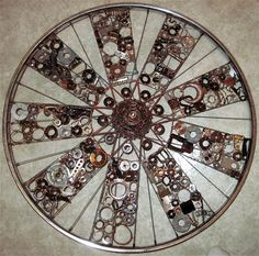The Cycle of Life, a mixed media assemblage by Deborah O'Keeffe of salvaged metal pieces woven with copper wire onto bicycle wheel, finished with polyurethane varnish.