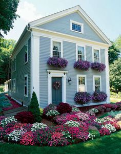 Small gray colonial with lush window boxes and landscaping