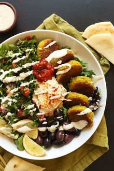 The ultimate Mediterranean Bowl with hummus, olives, parsley salad, falafel, and tahini sauce! My go-to recipe when we