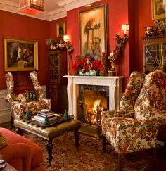 Holiday accessories find a home in this cheerful red room, where the mantel is festooned with cheerful poinsettias and berries. - Traditional Home ® / Photo: John Bessler / Design: Anthony Catalfano
