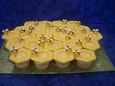 honey bee honey comb cupcakes - buttery vanilla yellow cupcakes, topped with buttercream dream icing, NFSC cut outs, rolled in yellow sanding sugar, put on top and center filled with honey. fondant bees held on top with a dab of buttercream.  made for a school class room, their class mascot is the bees