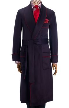 Our plain, pure cashmere dressing gown is made from the finest cashmere cloth, woven in Scotland. The rich navy cashmere cloth has a high lustre (characteristic of the finest cloth) and is rich in colour. It features two patch pockets and an outbreast welt. The gown is piped in red which is carried through to the pockets and belt. Made in England.