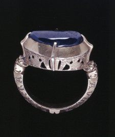 13th C. England. Finger-ring; gold; oval bezel, its sides decorated in openwork with engraved birds; set with a carbouchon sapphire held in four claws; the junction between bezel and hoop decorated with two animal heads; the hoop trapeziodal in section with beaded outer edge, the two sides engraved to receive a nielloed inscription: AVE MARIA GRA / TIA PLENA DMI. ('Hail Mary, full of the grace of the Lord'), a variation on the angelic salutation at the Annunciation.