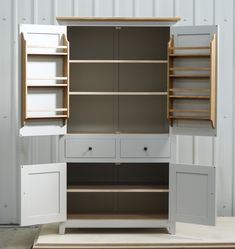 Larder cupboard handpainted in Farrow & Ball Estate Egshell - 'Pavilion Gray'. Tulip wood carcass with painted birch ply panels and maple faced birch ply shelves. Dovetailed oak drawers on high quality soft close runners. Oak spice racks. High quality solid brass hinges and adjustable brass shelf supports. Solid oak cornice and walnut knobs.