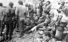 "1944 Omaha. A large group of American assault troops of the 3d Battalion, 16th Infantry Regiment, 1st U.S. Infantry Division, having gained the comparative safety offered by the chalk cliff at their backs, takes a ""breather"" before moving onto the continent at Colleville-Sur-Mer, Omaha Beach, in Normandy, France. Medics who landed with the men treat them for minor injuries."