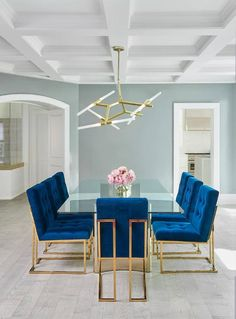 Jonathan Adler Goldfinger blue velvet dining chairs frame a stunning long glass dining table with a brass base featuring a curvy modern design.