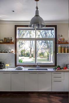 Cocina de una casa en Talar con muebles de cocina de frente blanco (Cato Cocinas), mesada de mármol de Carrara y piso de cemento alisado.