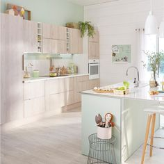 A medium size kitchen with light green high-gloss doors and drawers ...