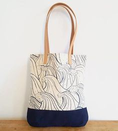 Printed with a hand-illustrated design, this canvas tote bag looks mighty fine on your shoulder, filled with the essentials. The canvas exterior is screenprinted in dark blue ink with a repeating pattern of cresting waves, and the bag is fully lined in natural cotton. It's finished with long leather straps for easy carrying of market hauls, library books or your trusty laptop—choose the waxed canvas bottom option for especially rugged wear.