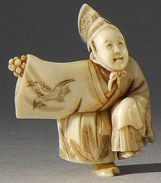 """IVORY NETSUKE Meiji Period Depicting a Sambaso dancer in a crane-decorated costume. Signed """"Masatsugu""""."""