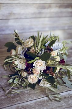 Peach Burgundy & White bouquet with mini pinecones is simply stunning. Florals by BW Events Photography by Leslie Marie