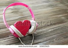 Pink headphones with rosy heart on wooden background - stock photo