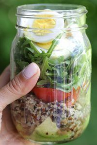 A protein-packed meatless salad in a jar made with quinoa lentils arugula avocado and hard boiled eggs are perfect to pack for work the beach picnics or anywhere you need a portable lunch on the go. Mason Jar Lunch, Mason Jar Meals, Meals In A Jar, Mason Jars, Taco Salat, Quinoa Salat, Salad In A Jar, Soup And Salad, Cobb