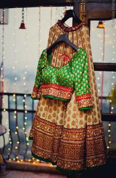 Attractive cream butta lehenga with heavy thread work border ,banaras blouse with elbow length sleeves.