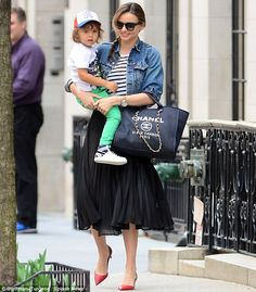 Lady of luxury: Miranda Kerr showed off her impressive strength as she juggled her son Flynn and her $3k Chanel tote in New York City on Mon...