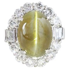 1930s Art Deco Cats Eye and Diamond Ring. This is an Art Deco ring from circa 1930s with a very fine and transparent Cat's Eye Chrysoberyl gem of 10.20 carats, surrounded by round and emerald cut diamonds of circa 1.50 carats. The Cat's Eye has the milk and honey colour and shows a beautiful eye in the center. C 1930s