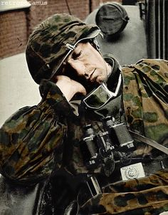 Quick nap for a Waffen SS grenadier in full camouflage kit and carrying the indestructible Zeiss field glasses, standard issue for the German army of the time. Note the truck's headlight cover visible behind the sleeping man. -