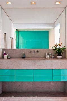 No banheiro o espelho cobre toda a largura da parede acima da pia e reflete a cor do vidro que reveste a superfície oposta. Projeto dos arquitetos Renato Salles e Vivian Giometti.