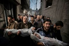 World Press Photo of the Year 2012 - Paul Hansen/Sweeden/Dagens Nyheter - Nov. 20, 2012, Gaza City, Palestinian Territories. Two-year-old Suhaib Hijazi and her three-year-old brother Muhammad were killed when their house was destroyed by an Israeli missile strike. Their father, Fouad, was also killed and their mother was put in intensive care. Fouad's brothers carry his children to the mosque for the burial ceremony as his body is carried behind on a stretcher.
