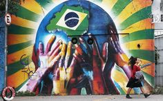 Pin for Later: Brazil Gears Up For the World Cup  A woman walked past the colorful graffiti wall marked with a Brazilian flag in São Paulo.
