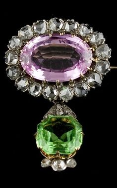 A Suffragette brooch, circa 1910. Surmounted by an oval pink topaz framed by diamonds, suspending a detachable peridot drop, and mounted in yellow gold and silver. The green white and purple colours representing the WSPU; the Women's Social and Political Union.