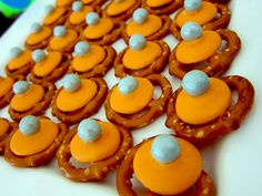 Meteoroids---Simple pretzels, topped with orange candy melts.  Pop in a 350 degree oven for 2 minutes until the candy melts start to melt.  Remove them from the oven and place silver sixlets on top.  Let them cool in a cool spot or in the fridge, then store in an airtight container until ready to use.