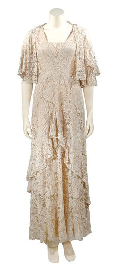 Doucet Beige Chantilly Lace Ensemble   French, early 1930s   The slender sleeveless design with draped bateau neckline extending to V-back, the skirt with asymmetrical bias ruffle above hem meeting at high point center back, nude tulle and china silk underlay, lace jacket with tiered bell sleeve