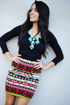 Black staple top, patterned skirt, statement necklace.