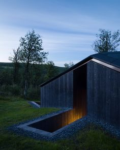 The Geilo Cabin comprises a main dwelling with a guest house and carport, which are connected by a continuous gabled roof and arranged in a U-shaped plan around a sheltered courtyard.