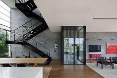 לגובה הבית נמתח חלל פתוח שבו גרם מדרגות מפלדה שחורה, שחלקיו הובאו לאתר הבנייה מוכנים ורותכו במקום. המדרגות נראות כאילו הן תלויות באוויר, ללא תמיכת קיר אריחי הסיליקט שלצידן ( צילום: עמית גרון )